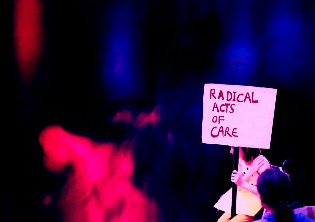 Photograph of Fitz' 'Radical Acts of Care' project. Fitz sits on a chair, with one hand on her shoulder, and the other holding a sign with the words 'Radical Acts of Care' written in red on a white background. The rest of the photo is a blur of pink and blue lights in a black space.