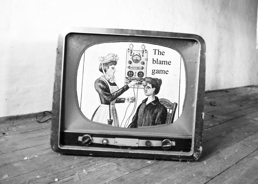 Black and white drawing of a Victorian tending to a female patient sat in a chair, by using an electric machine from the wall. The words 'the blame game' are written next to the machine. This image is placed on the screen of an old-fashioned tv, sitting on the floor of an empty room.