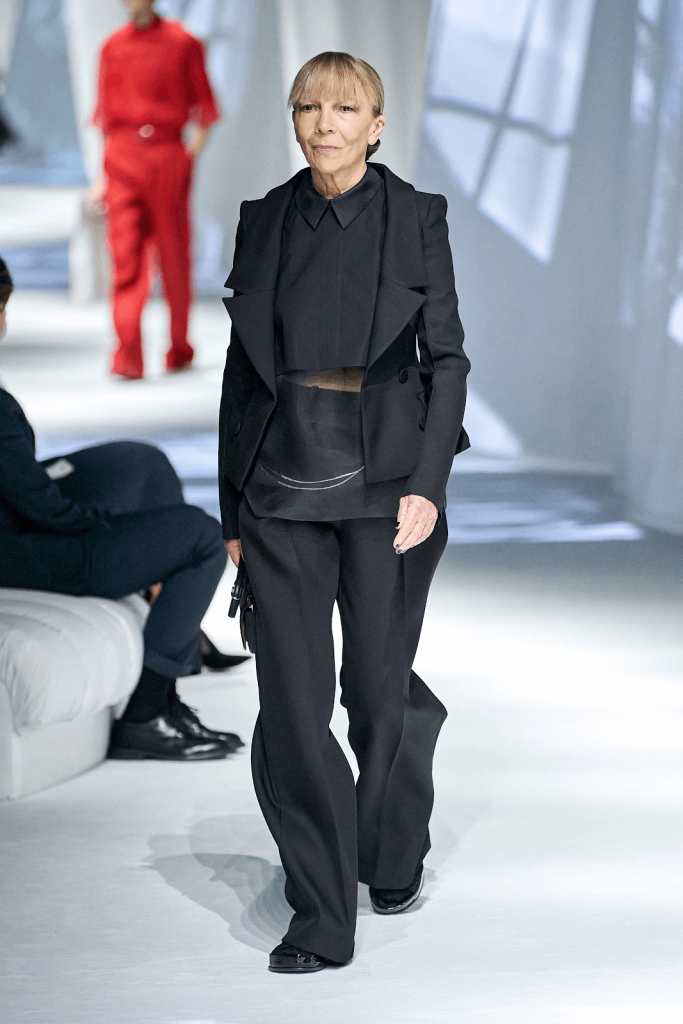 ID: A model with a blonde fringe and hair in a low bun walks a white runway, wearing a black two-piece suit with a cropped, collared black shirt, black patent shoes and a black purse. Image courtesy of Fendi via fendi.com/us/woman/highlights/spring-summer-2021/spring-summer-2021-looks