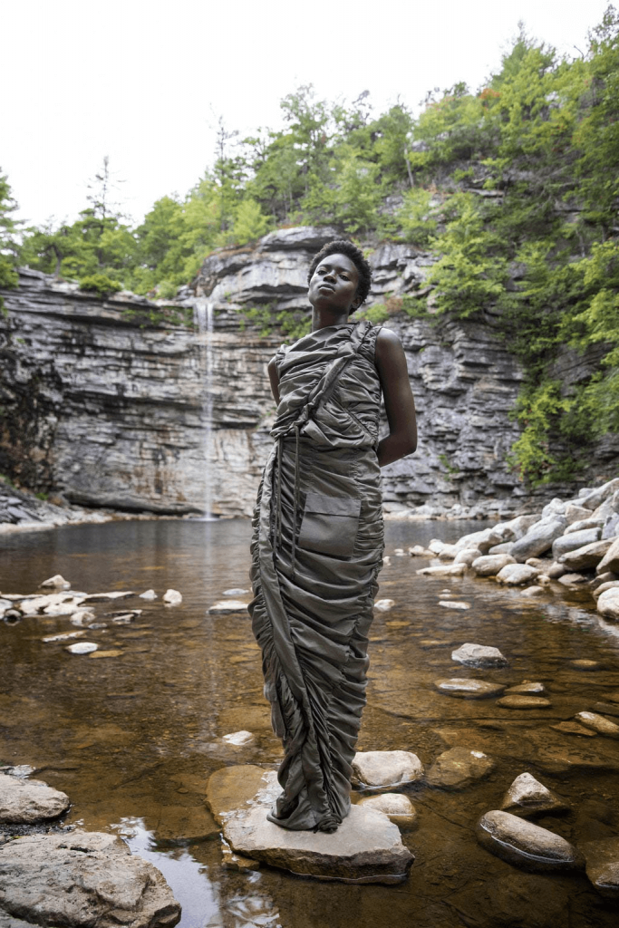 ID: A model standing on a stone in front of a small waterfall and rockfront, wearing a full-length, sleeveless, stone-coloured dress. Image by Who Decides War via runway360.cfda.com/designers/who-decides-war/a-still-small-voice/#look-15