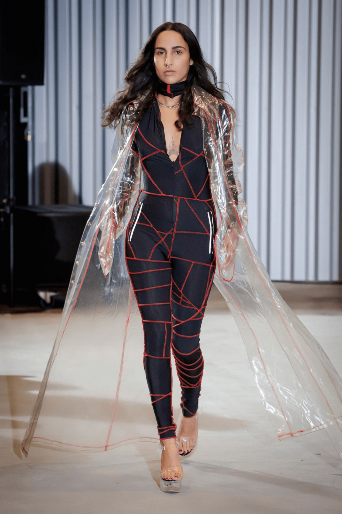 ID: A model with shoulder-length brown hair walks a runway, dressed in a form-fitting navy jumpsuit decorated with a red contrast stitch. They also wear a floor-length clear PVC cape with similar contrast stitch and clear platform heels. Photo courtesy of XULY.Bët via woman.es/galerias/moda/xuly-bet-paris-mujer-primavera-verano-2021?id=51199-3218467